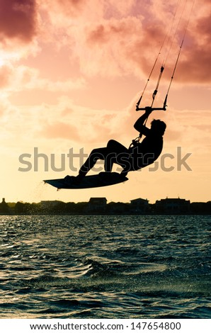 Silhouette of a kitesurfer flying above the water at sunset - stock photo