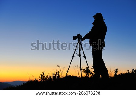 Silhouette of a landscape photographer in twilight