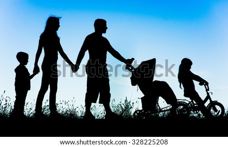 silhouette of a large family that walks at sunset.