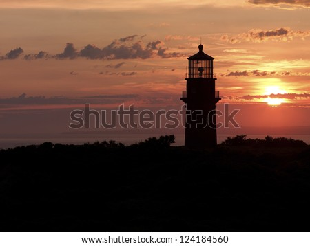 Silhouette of a lighthouse during sunset. - stock photo