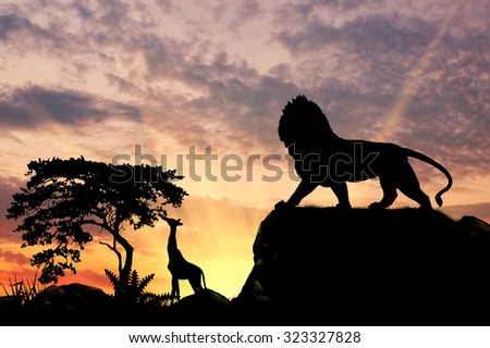 Silhouette of a lion on a hill at sunset savanna - stock photo