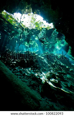 Silhouette of a lone female snorkeler from inside an underwater cave system in mexico.