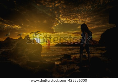 Silhouette of a lonely girl on the bank looking at the sunset over the water
