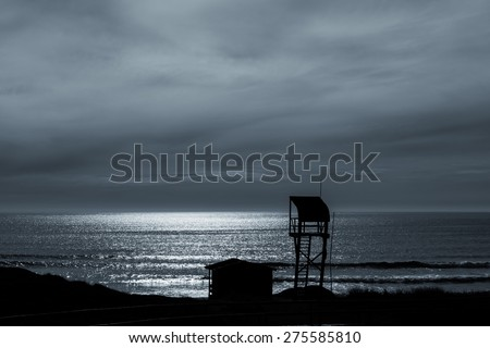 Silhouette of a lonely lifeguard station in Galicia at dusk overlooking the Atlantic Ocean. - stock photo