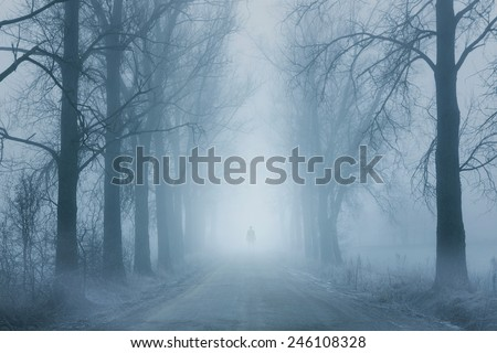 Silhouette of a lonely man standing on the foggy road - stock photo