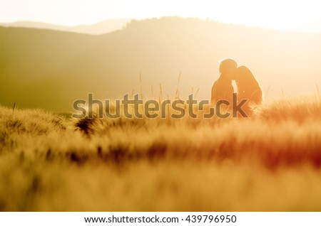 Silhouette of a loving couple at sunset in a wheat field. Couple kissing at summer sunrise light.  Beautiful postcard or wallpaper with love, relationship theme  - stock photo