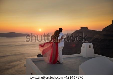 Silhouette of a loving couple on the background of the setting sun, mountains, islands and sea. Santorini. Greece. Just married. Walk at sunset. Walk through the mountains at sunset. Santorini sunset - stock photo