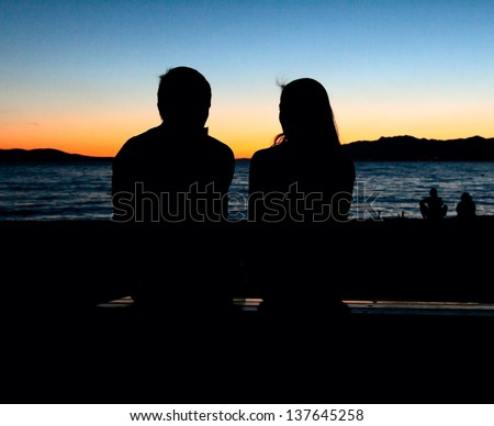 silhouette of a loving couple sitting on a bench at sunset - stock photo