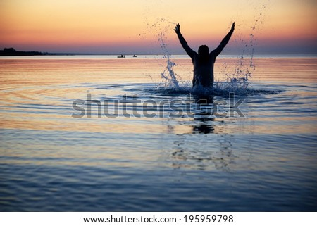 Silhouette of a male jumping with raised arms in the water