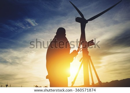 Silhouette of a male surveyor standing with theodolite against electric generator and evening sky while measuring the distance for the construction of a new highway, man geo desist working outside  - stock photo