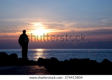 Silhouette of a man admiring sunset over italian sea - negative space on the right