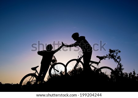 Silhouette of a man and girl on mountain bike at sunset  - stock photo