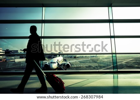 Silhouette of a man at the Airport with Suitcase - stock photo