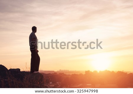 Silhouette of a man at the beautiful sunset on the mountain. Background - stock photo