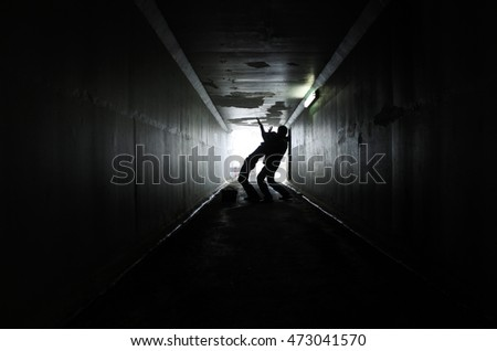 Silhouette of a man attacks  a woman from behind in a dark tunnel. Violence against women concept. copy space