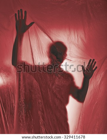 Silhouette of a man behind a red transparent plastic - stock photo