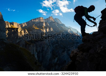 Silhouette of a man climbing in the mountains - stock photo