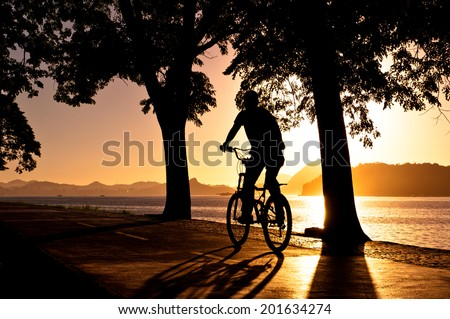 Silhouette of a Man Cycling in the Early Morning during Beautiful Warm Sunrise in Rio de Janeiro - stock photo