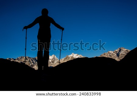 Silhouette of a man enjoying the view of the mountains in the morning - stock photo