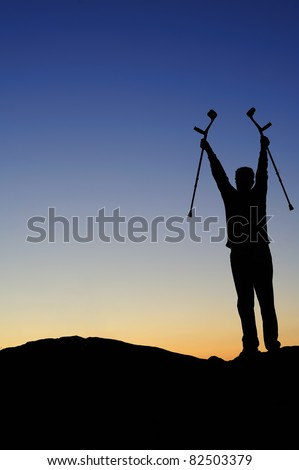Silhouette of a man facing the dawn holding his crutches high above his head, greeting the sunrise. - stock photo