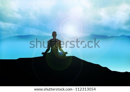 Silhouette of a man figure meditating on the mountain - stock photo