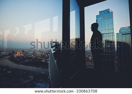 Silhouette of a man financier think about something while standing near office window background with copy space for your text message or advertising content, young male thoughtful rest after briefing - stock photo
