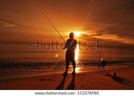 Silhouette of a man fishing at the beach