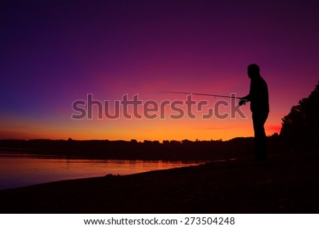 Silhouette of a man fishing on the lake shore at sunset
