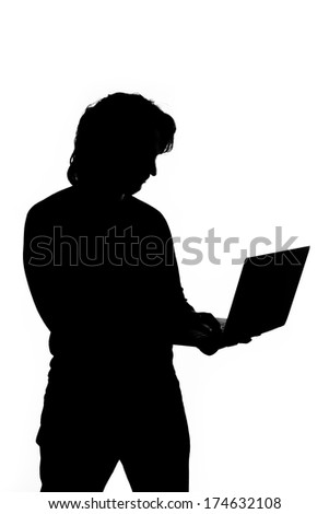 Silhouette of a man holding laptop - stock photo