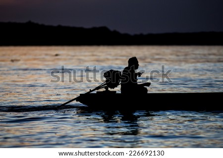 """Silhouette of a man in a canoe called """"peque peque"""", in the Ucayali river. Loreto, Iquitos, Peru - stock photo"""