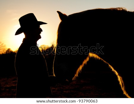 Silhouette of a man in a cowboy hat with his horse against sunset sky - stock photo