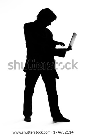 Silhouette of a man in suit typing on a laptop - stock photo
