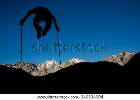 Silhouette of a man jumping high above mountain ridge - stock photo