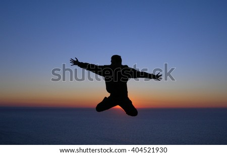 Silhouette of a man jumping in front of the sunset in the ocean. Concept photo of happiness, freedom and lifestyle. - stock photo