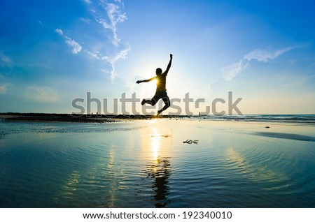 Silhouette of a man jumping over sun rising up - stock photo