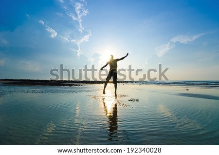 Silhouette of a man jumping over sun rising up