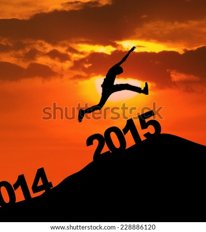 Silhouette of a man jumping over the new year 2015 at sunrise - stock photo