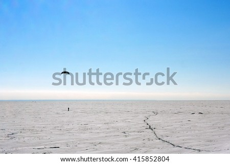 Silhouette of a man kiting in winter time at frozen lake - stock photo