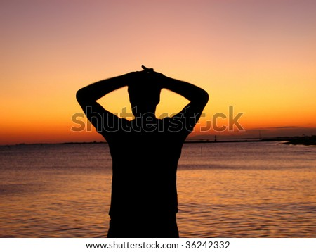 Silhouette of a man looking at the sunset over the ocean