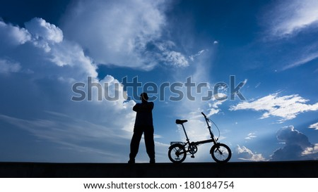 Silhouette of a man looking up at the camera posed with his folding bike.