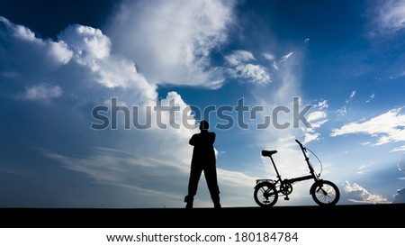 Silhouette of a man looking up at the skies posed with his folding bike. - stock photo