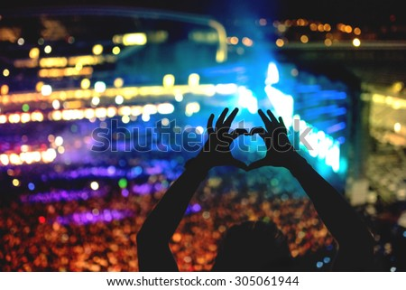Silhouette of a man making heart from hand gestures, vintage look on photo and crowd background - stock photo