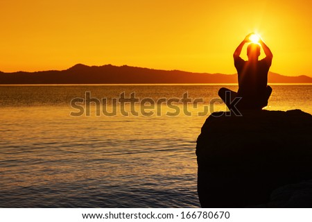 Silhouette of a man meditates on the stone above a sea, holding a sun, sunset light. Copy space