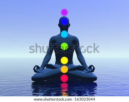 Silhouette of a man meditating with seven colorful chakras upon ocean by blue light - stock photo