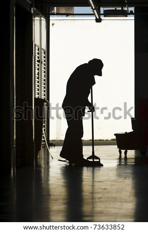 Silhouette of a man moping warehouse floor - stock photo