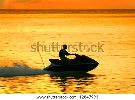 silhouette of a man on a waverunner - stock photo