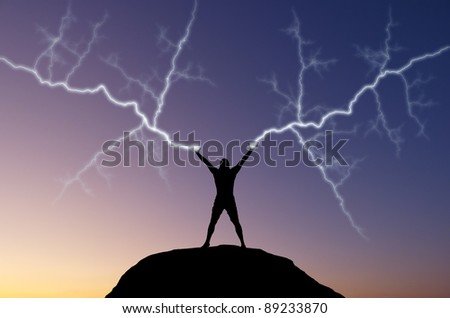 silhouette of a man on the hill out of the hand produces lightning. natural composition - stock photo