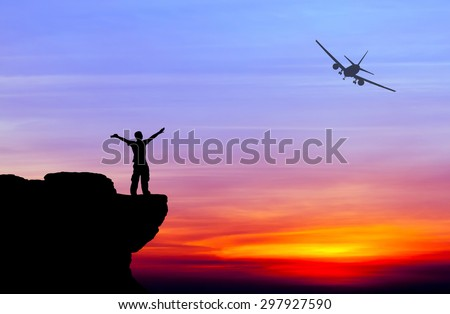 Silhouette of a man on the rock and silhouette commercial plane flying at sunset - stock photo