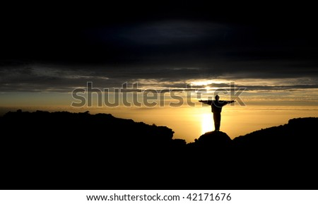 Silhouette of a man on top of a mountain at sunset