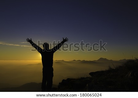 Silhouette of a man on top of a mountain, raising his hands in joy./ Happy hiker - stock photo